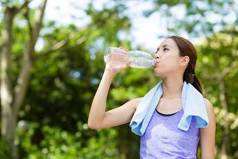 Athlete woman drinking water from a plastic bottle