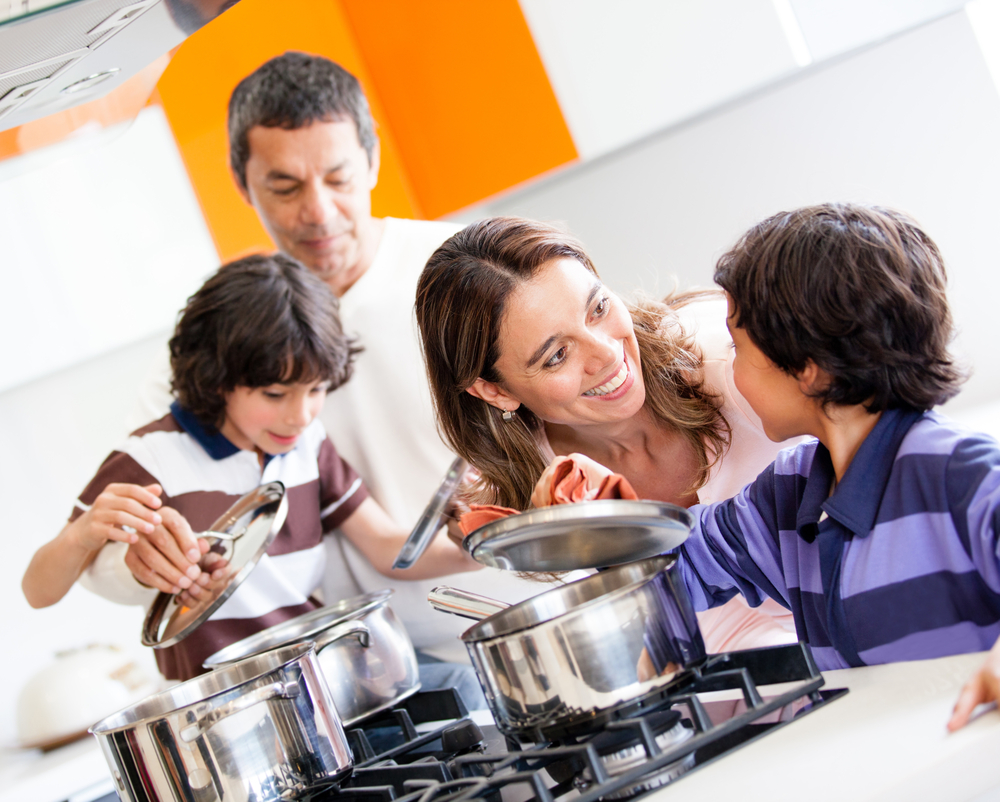 Family cooking together in the kitchen and looking happy