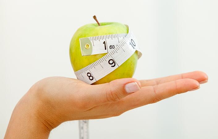 Hand holding an apple with a measuring tape around it isolated over a white background.jpeg