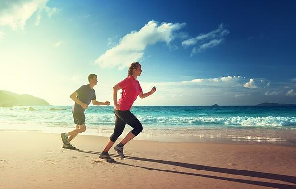 Man and women running on tropical beach at sunset .jpeg