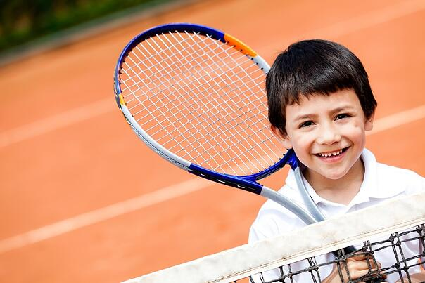 Young boy playing tennis at a clay court.jpeg